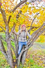 Cute girl in autumn sit on tree