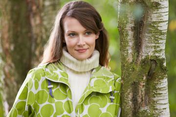 Woman Wearing Raincoat Walking In Woods