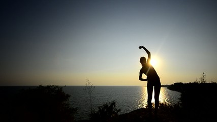 Silhouette Of A girl exercising at sunset near ocean