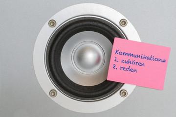 "Lautsprecher mit rosa Haftnotiz ""Komunikation"""