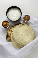 top view of poppadums and naans served with raita and chutney