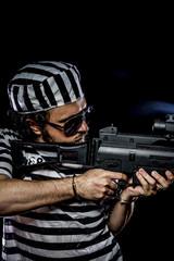 disorders .Prison riot concept. Man holding a machine gun, priso