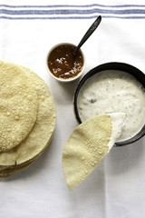 tTop view of poppadums with raita and mango chutney