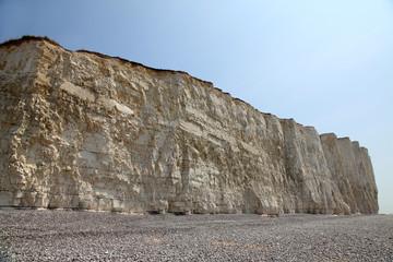 Beach head chalk cliffs and pebble beach against blue sky