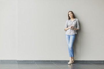 Woman with tablet by the wall