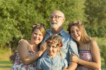 Outdoor portrait of  grandfather with granddaughters.