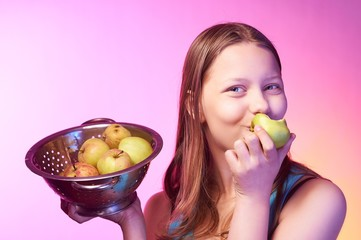 Teen girl holding a colander full of apples and eating an apple