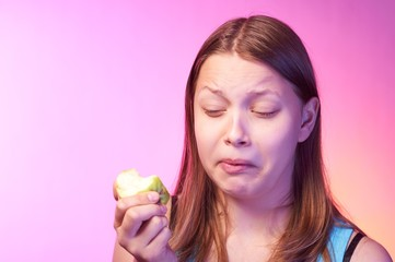 Teen girl eating disgusting apple