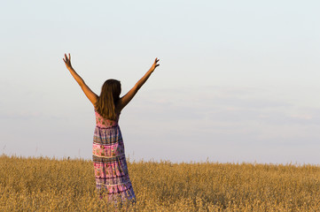 The girl put hands up standing in oat field.