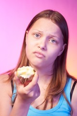 Unhappy teen girl eating tasteless apple