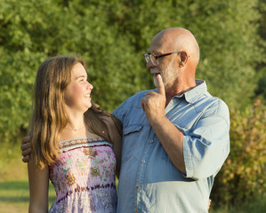 Outdoor portrait of  grandfather with granddaughter.