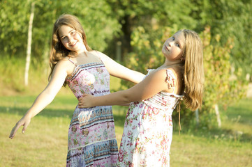 Two girls is dancing in a garden.
