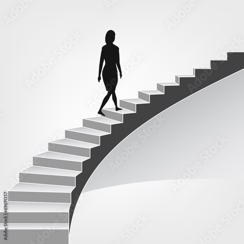 woman walking up on spiral staircase - 69691357