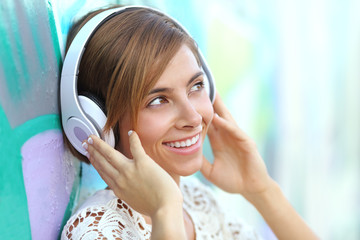 Happy woman with headphones listening to the music
