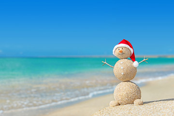 Sandy snowman in santa hat. Holiday concept