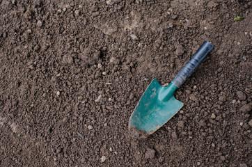 small spade on garden soil