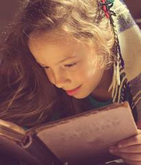 Vintage portrait of cute curly school girl reading a book
