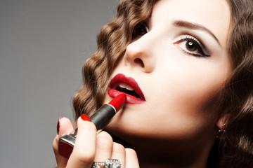 Applying lipstick. Close up portrait