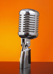 Classic microphone on orange background