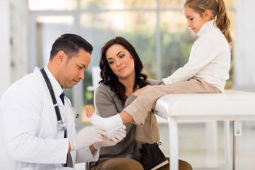 paediatrician bandage little patient's ankle