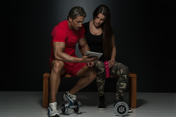 Fit Attractive Young Couple Looking At A Tablet