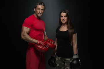Young Couple Wearing Boxing Gloves And Smiling