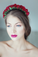 Young beautiful woman with flowers in hair and blue eyes
