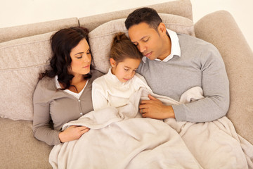 family sleeping together on the couch