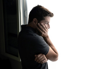 attractive man looking through window suffering depression