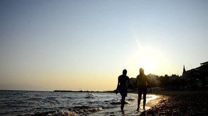 Young Teen Couple Walk on Ocean Beach Sunset