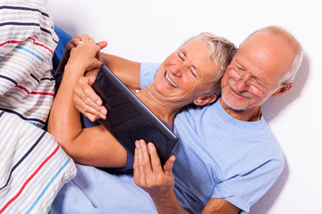 Senior Couple with Tablet and Newspaper in Bed