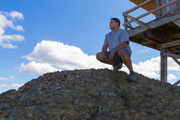 Man Crouched Atop Granite Rocks