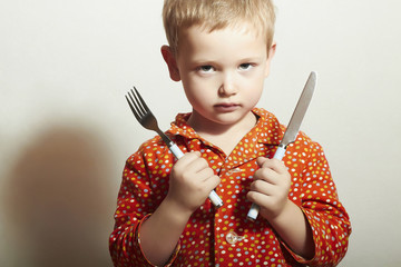 Angry child. hungry little boy with Fork and Knife.Food