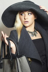 Beautiful Blond Woman in Black Hat.Handbag.Shopping panic.Autumn