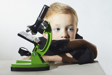 little boy don't want to study.child with microscope.Education