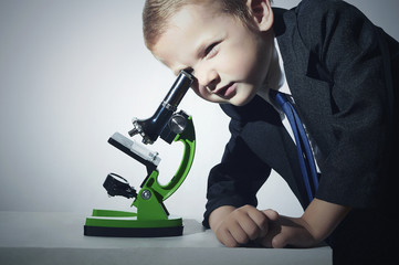 boy in suit looking in microscope.child.Schoolboy.Education