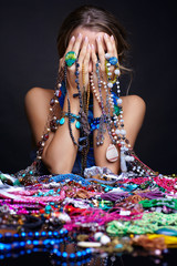 Woman crying over heap  of  jewelry and bijouterie