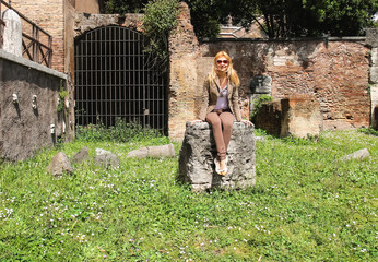Attractive girl near the picturesque ruins of Rome, Italy
