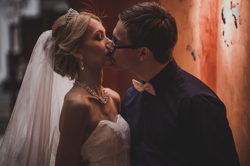 portrait of bride and groom kissing in tunnel