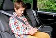 Kind mit Tablet-Computer im Auto
