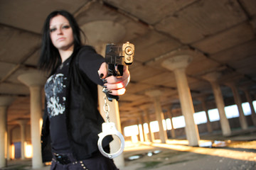 Girl with guns in abandoned ruins