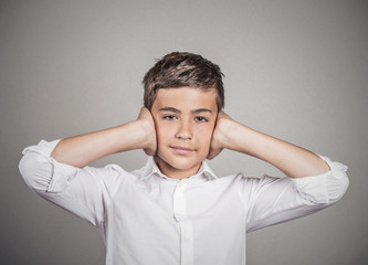 Boy covering ears with hands. Hear no evil concept