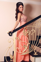 beautiful bride in elegant coral dress posing on stairs