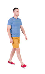 Back view of going  handsome man in shorts.  walking young guy