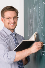young teacher and classic chalkboard background.