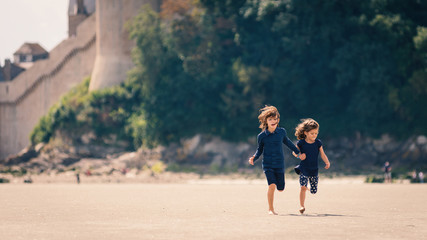 Young sisters running on the beach in front of Mont Saint Michel