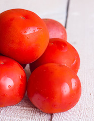 raw red tomatoes on a white wooden board