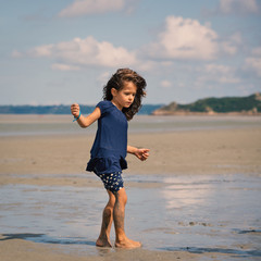 Young girl walking on the beach in front of Mont Saint Michel an