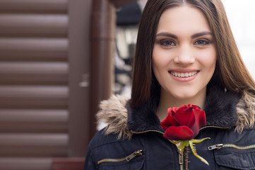Pretty young brunette woman and red rose.
