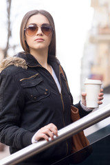 Young brunette woman outdoors with coffee.